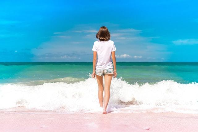 girl walking into waves